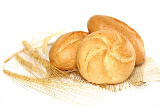 Verse broodjes op plundering en tarwe oor op witte ondergrond Premium Foto