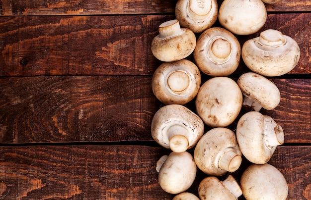 Verse champignonpaddestoelen op houten lijst, hoogste mening. kopieer ruimte Premium Foto