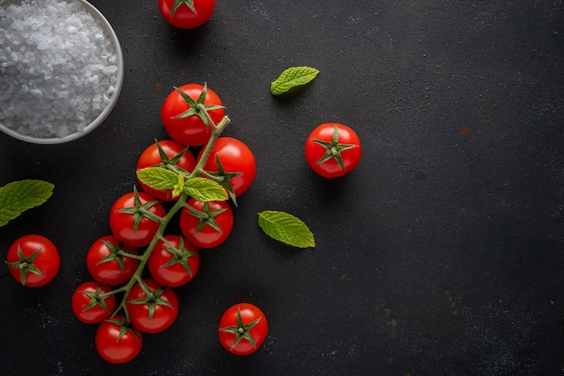 Verse cherrytomaatjes op een zwarte met kruiden. Premium Foto