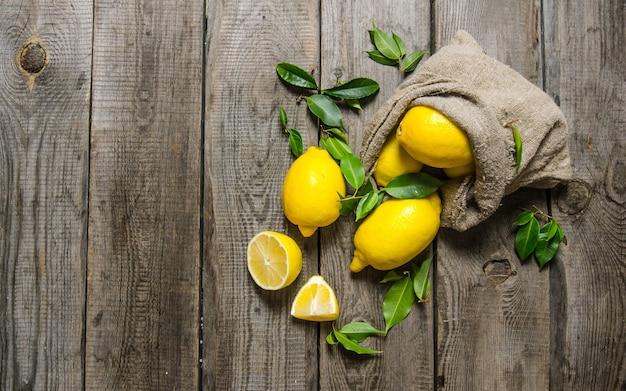 Verse citroenen in een oude zak met bladeren. op houten achtergrond. vrije ruimte voor tekst. bovenaanzicht Premium Foto