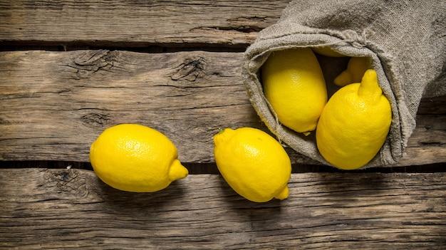 Verse citroenen in een oude zak. op een houten achtergrond. bovenaanzicht Premium Foto