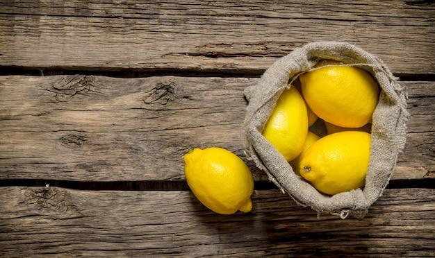 Verse citroenen in een oude zak. op een houten achtergrond. vrije ruimte voor tekst. bovenaanzicht Premium Foto