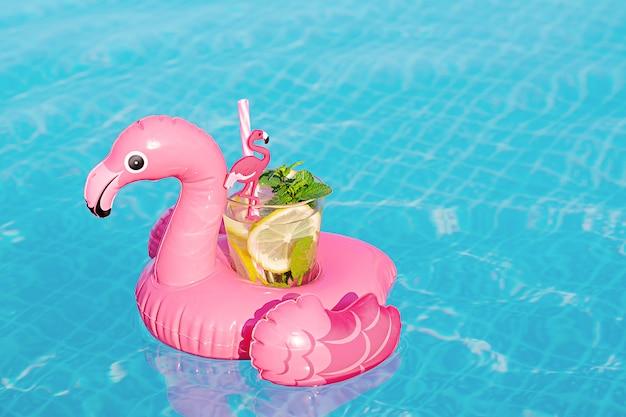 Verse coctailmojito op opblaasbaar roze flamingostuk speelgoed bij zwembad. vakantie concept. Premium Foto