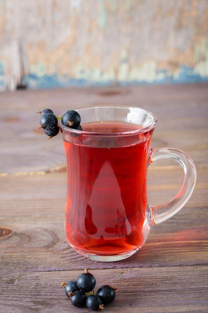 Verse compote van rijpe zwarte bessen in een glas op een houten tafel Premium Foto