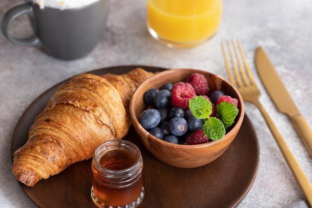Verse croissant, koffie met melk, bessen, siroop en sinaasappelsap. Premium Foto