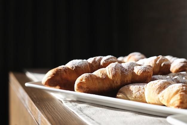 Verse croissants met croissant met poedersuiker op een houten tafel Gratis Foto