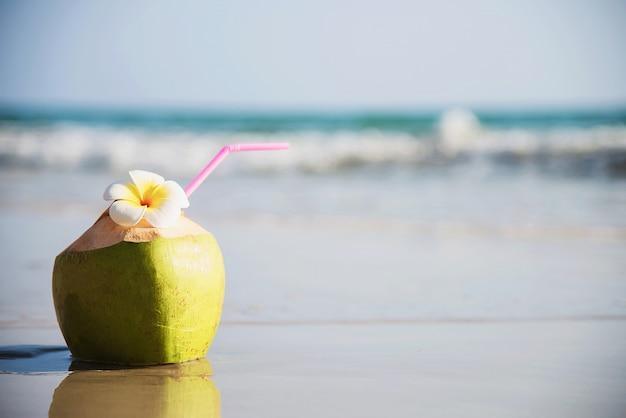 Verse die kokosnoot met plumeriabloem op schoon zandstrand met overzeese golf wordt verfraaid - vers fruit met van de overzeese het concept zonvakantie Gratis Foto
