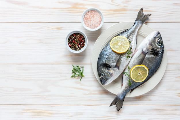 Verse doradovissen met kruiden, olijfolie, knoflook en kruiden op witte schotel op witte lijst. Premium Foto