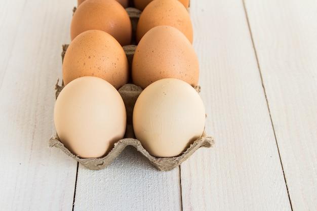 Verse eieren in kartonpakket op wit hout Gratis Foto