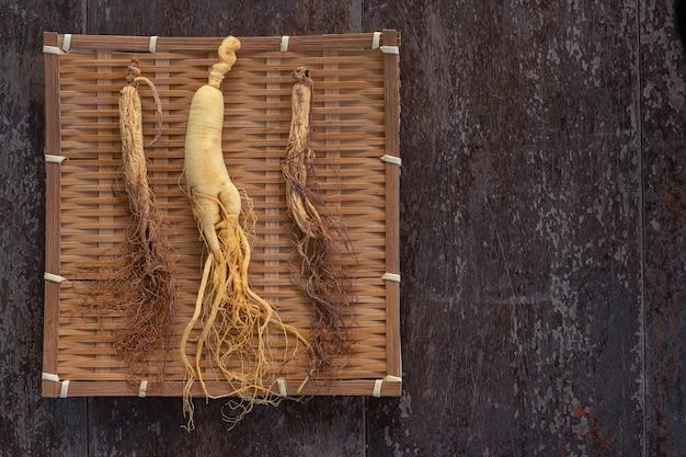 Verse en droge ginseng op bamboeweefsel met exemplaarruimte op de houten achtergrond. Premium Foto