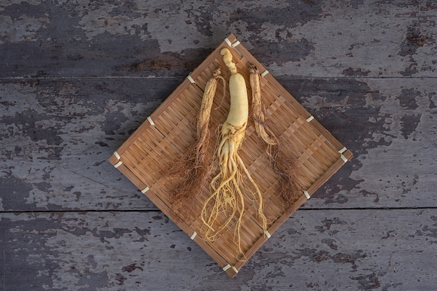 Verse en droge ginseng op bamboeweven met de houten achtergrond. Premium Foto