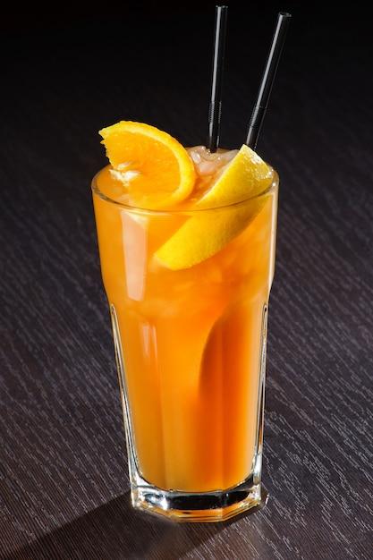 Verse exotische cocktail met ijsblokjes en sinaasappel op een houten tafel Premium Foto