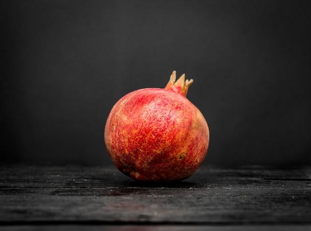 Verse gehele granaatappel op een zwart dicht hout Gratis Foto
