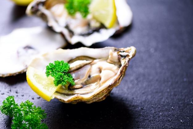 Verse geopende oesters, citroen, kruiden, ijs op donker metaal. bovenaanzicht, kopie ruimte Premium Foto