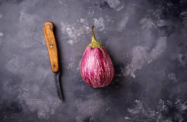 Verse gestreepte purpere aubergines op grijze achtergrond Premium Foto