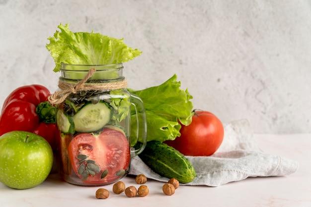Verse gezonde plantaardige plak in metselaarkruik met vruchten en hazelnoot Gratis Foto