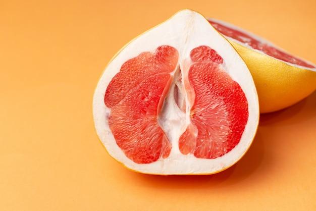 Verse grapefruit op een oranje oppervlak, close-up. geslacht concept. het concept van de gezondheid van vrouwen. Premium Foto