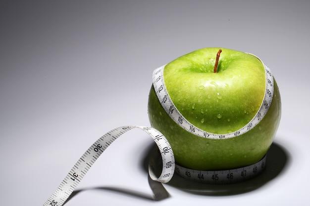 Verse groene appel met meetlint Gratis Foto