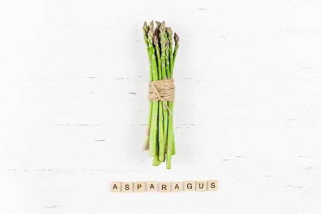 Verse groene asperges op witte houten oppervlak Premium Foto
