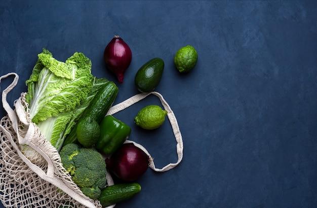 Verse groene en paarse boodschappentas op een donkerblauwe achtergrond Premium Foto