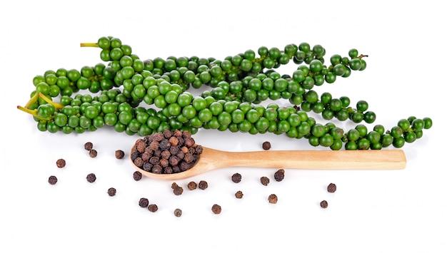 Verse groene peperbollen en zwarte peperbollen die op wit worden geïsoleerd Premium Foto