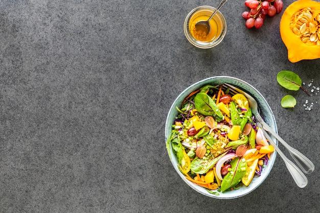Verse groente- en fruitsalade in een plaat op een zwarte stenen tafel. bovenaanzicht Gratis Foto