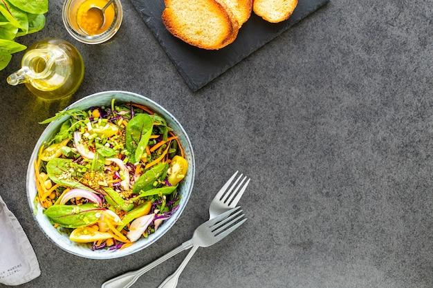 Verse groente- en fruitsalade in een plaat op zwarte stenen ondergrond Gratis Foto