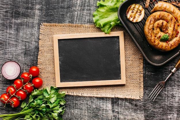 Verse groente en spiraalvormige geroosterde worsten met lege lei op grijze geweven achtergrond Gratis Foto