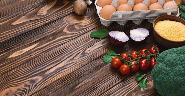 Verse groenten; eieren en polenta kom over houten bureau Gratis Foto