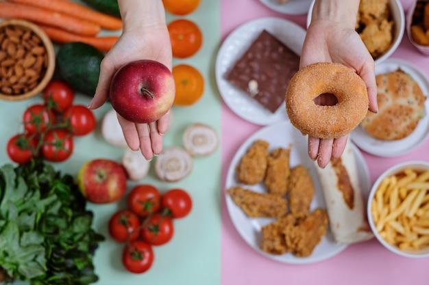 Verse groenten en fruit tegen junkfood Premium Foto