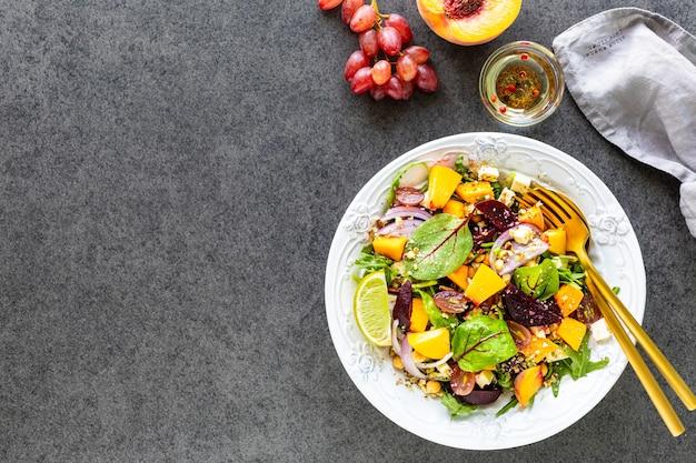 Verse groentesalade met bieten, rucola, rode ui, zuring, kikkererwten, perzik en druiven in een witte plaat Gratis Foto