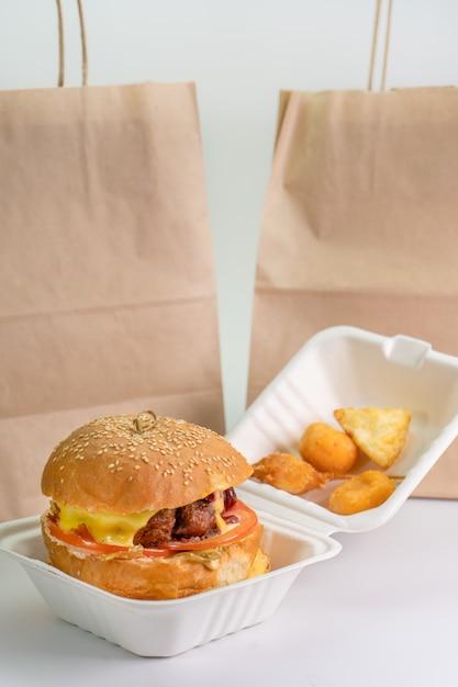 Verse hamburger in eco verpakking, fast food, geïsoleerde witte achtergrond. levering van hamburger, burger Premium Foto