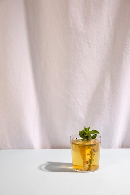 Verse heerlijke drank met muntblad tegen wit gordijn Gratis Foto