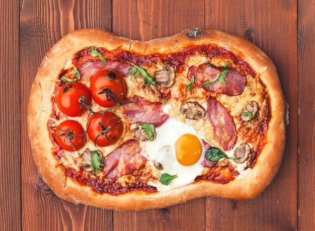 Verse heerlijke pizza uit de oven met ei, prosciutto en tomaat Premium Foto