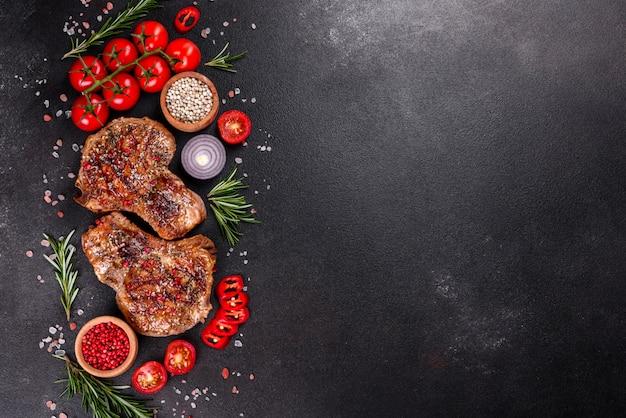 Verse heerlijke sappige biefstuk op de botten met groenten en kruiden. grill van het varkensvlees de sappige lapje vlees op donkere lijst Premium Foto