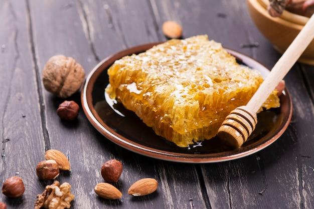 Verse honingraat en assortiment van noten op zwarte houten achtergrond. Premium Foto