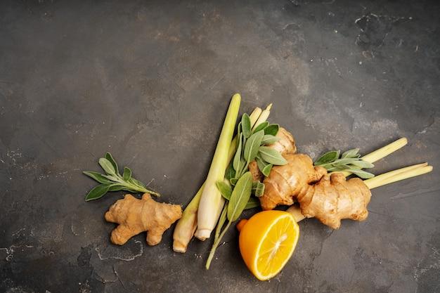 Verse ingrediënten gember, citroengras, salie, honing en citroen voor gezonde antioxidant en ontstekingsremmende gemberthee op donkere achtergrond met kopie ruimte. bovenaanzicht Premium Foto
