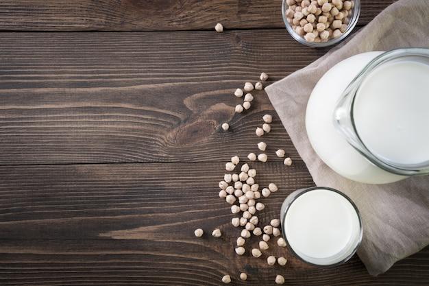 Verse kikkererwtenmelk in glas en waterkruik op donkere houten lijstachtergrond. rustieke stijl. Premium Foto