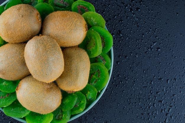 Verse kiwi met gedroogde kiwi in een plaat op een donkere grijze achtergrond, plat lag. Gratis Foto