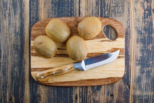 Verse kiwi met mes plat lag op houten en snijplank achtergrond Gratis Foto