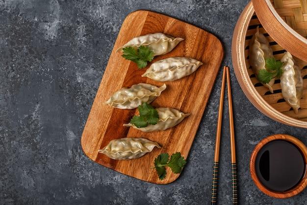 Verse knoedels op een donkere stenen ondergrond aziatische keuken, bovenaanzicht, kopie ruimte. Premium Foto