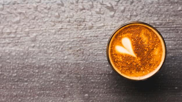 Verse koffie met hart latte kunst op waterdruppel achtergrond Gratis Foto