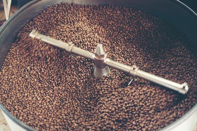 Verse koffiebonen in braadstukmachine, arabica geroosterde koffie Premium Foto