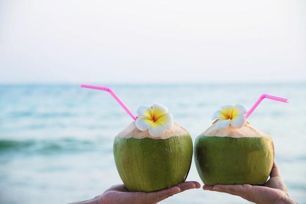 Verse kokosnoot in paarhanden met plumeria die op strand met overzeese golf wordt verfraaid - de toerist van het wittebroodswekenpaar met vers fruit en overzees het concept van de zonzonvakantie Gratis Foto