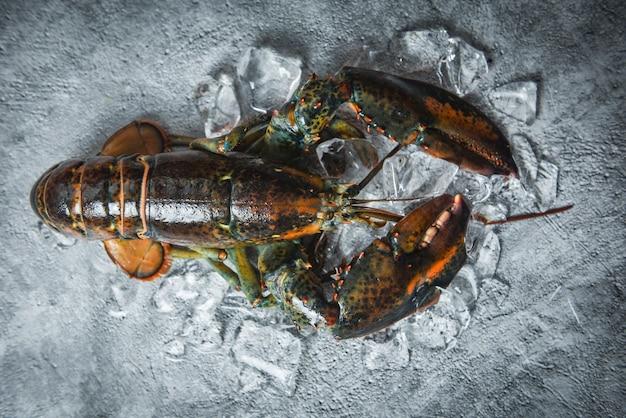 Verse kreeft schelpdieren in het visrestaurant voor gekookt voedsel rauwe kreeft op ijs op een zwarte stenen tafel Premium Foto