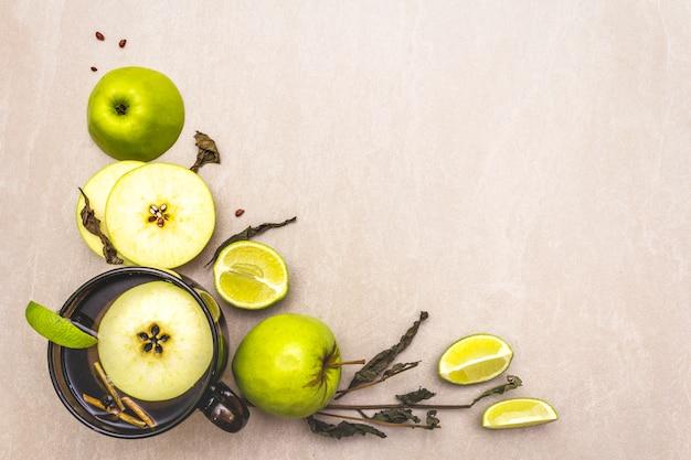 Verse limoen en appel, kopje thee en droge kruiden Premium Foto