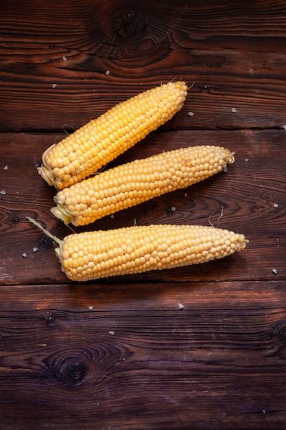 Verse maïs op een donkere houten tafel. bovenaanzicht. Gratis Foto
