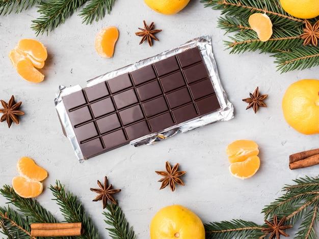 Verse mandarijnen met takken van kerstboom, de kaneel van de steranijschocolade op grijs beton, exemplaarruimte Premium Foto