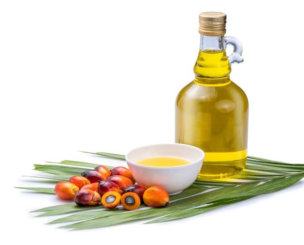 Verse oliepalmvruchten en koken palmolie in glasflessen op palmbladen die op de witte ruimte worden geïsoleerd. Premium Foto