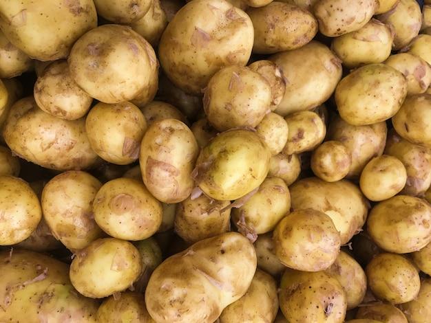 Verse organische aardappels op tribune op supermarktachtergrond Premium Foto